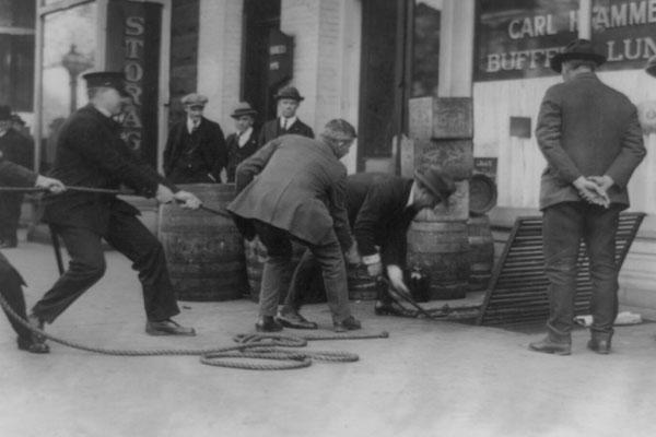 Men pulling on rope leading into underground shelter