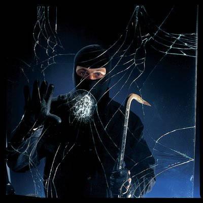 Man in all black looking through broken window with crowbar