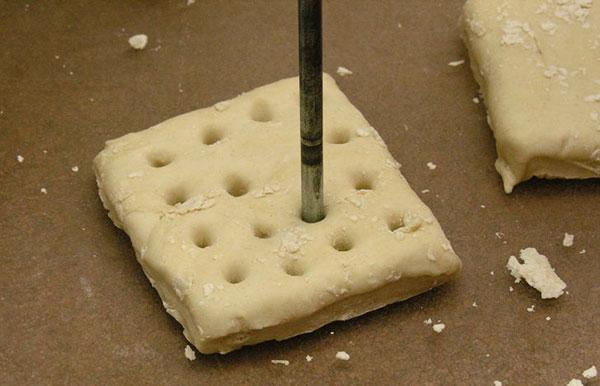 Small rod poking holes in hardtack dough