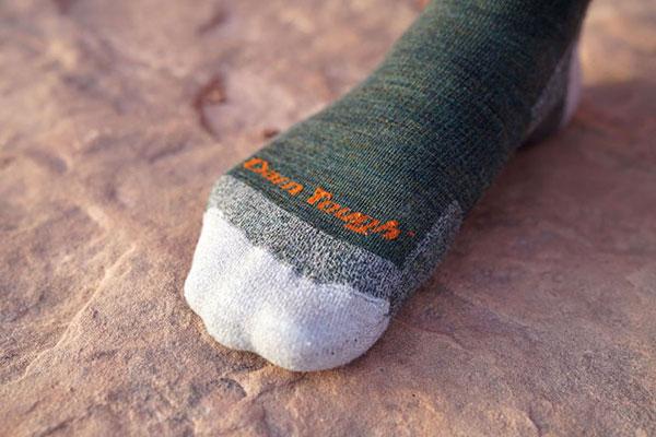 Foot wearing green Darn Tough hiking socks