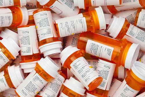 Orange bottles with white lids of prescription medications