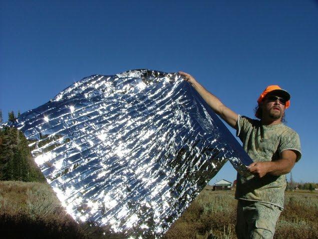 man unfolding an emergency blanket